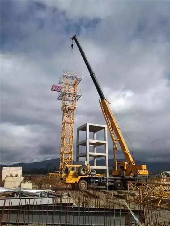 位于印尼苏拉威西岛的万向镍业工业园内,25吨汽车起重机正安装徐工塔机
