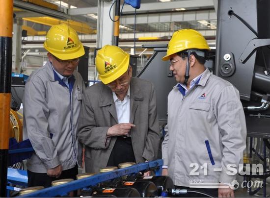 山东临工总经理文德刚(右)陪同原机械工业部副部长沈烈初(中)参观临工