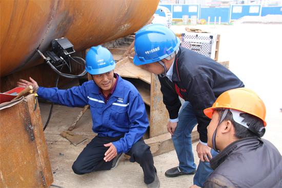曹晶(左)与厂家人员一起研究钢管全自动焊接技术