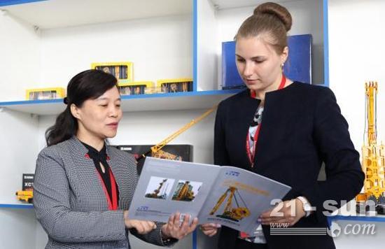 当地时间6月5日,徐工集团进出口公司党委书记蒋南(左)在讲解徐工集团参展产品。(王修君 摄)