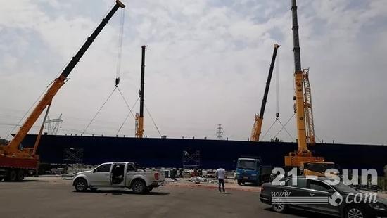 4台徐工XCT90正在合力起吊一个重达116吨,跨度70米的钢箱梁