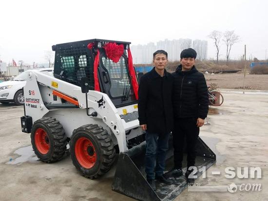张峰(左)和他的山猫沃福S16滑移装载机