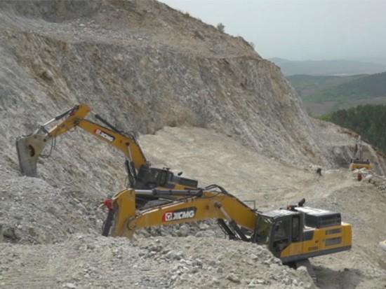 徐工XE490DK挖掘机在10米多高的山上修整梯形斜面