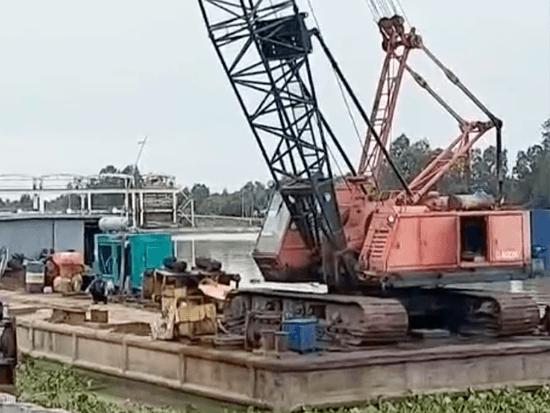 岸邊施工現場,起重機操作振動錘如何工作的,將混泥土樁打入水下!